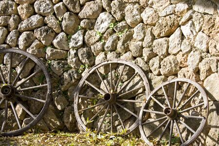 old wood farm wagon: Old wooden wheels leaning up against stone wall Stock Photo