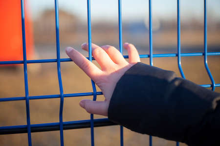 Hand on a fence grate. Girls palm on the fence.