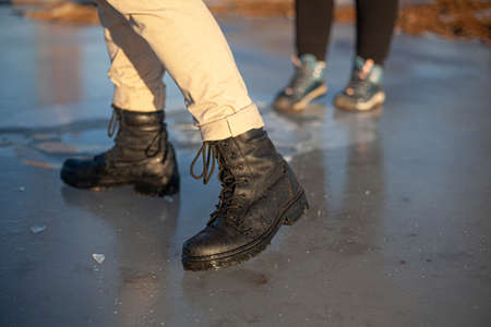 Army boots in the winter. A girl is standing on the ice.