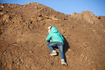 A girl is climbing a mountain. The child is dirty clothes.