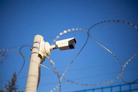 Surveillance camera on the fence. Video security.