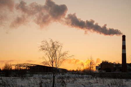 Smoke comes from the chimney. The plant stands in the field. Industrial landscape at sunset. Smoke emissions in the air. Air pollution. Burning garbage. Environmental issues in the city. High pipe. 写真素材