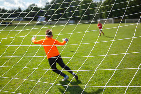 Goalkeeper catches the ball. Goal net in focus. Sports competition. Children's football on the field. Physical development. Children's sport. Sleight of hand. Ball Championship.