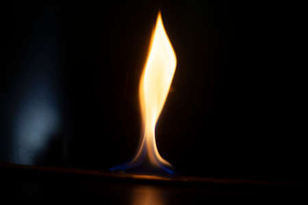 Tongue of fire flame in the dark. Ignition of oxygen in space. Fiery background. Fire of ether in the absence of light. Abstract fire heat background. Single fire. The ignition gel is on.
