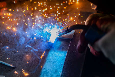 Metal welding. Sparks from electric heating. Work in the workshop. Creation of reliable fastening of materials. Fabrication of iron. The work of the master of metal.