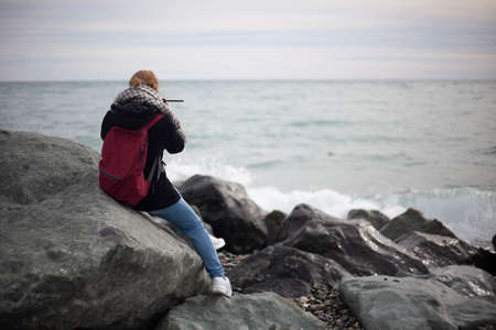 A girl on the seashore sits on a large stone. A romantic lady came ashore to mourn on a rock. A woman with a camera is shooting the sea. A good mood will come after a walk among the stones.