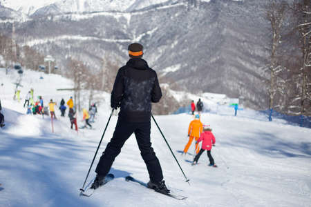 A skier rides on a snowy slope. Active rest in the winter. The athlete is preparing for the descent. Mountain ski resort. Outdoor activities on a winter vacation. The best time of the season. Man in a suit protecting from snow. Banco de Imagens
