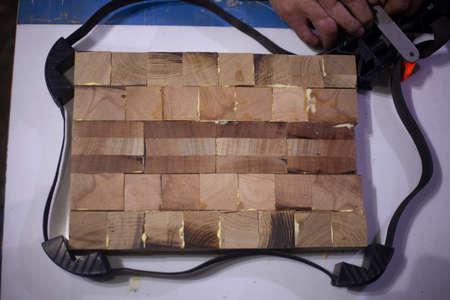 Bonding wooden cubes into one board. Creating a unique wooden product for cutting meat and vegetables. Joinery in the workshop. Sizing details. Woodwork. Do-it-yourself hobbies.