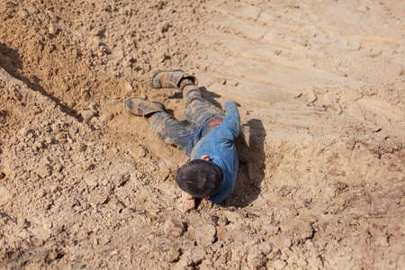 The boy is lying in the sand. The kid is dirty clothes. The boy fell in the sandbox. Naughty child having fun. A child without movement after falling. Rest of the child without the Internet. The usual walk with the children.