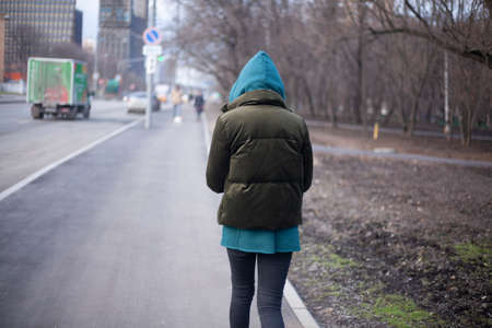 A girl is walking around the city. A teenager walks alone. Unknown person in the hood. The man did not wait for the bus and goes along the road. Shooting from the back. A woman walks aimlessly on the sidewalk. Imagens