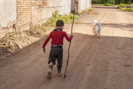The boy walks on the street. The child went on a trip. Hyperactive childhood. The kid got lost. Adventures in a young boy. Little mischievous person lives without internet.