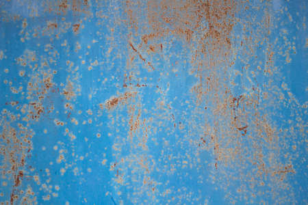 Rusty background. Poorly painted surface. The texture of the old metal structure. Simple background from abstract strokes of paint and oxidized steel.