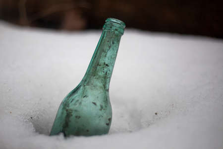 Bottle in the snow. A blue glass container is immersed in a layer of frozen water. Simple background discarded beer bottle.