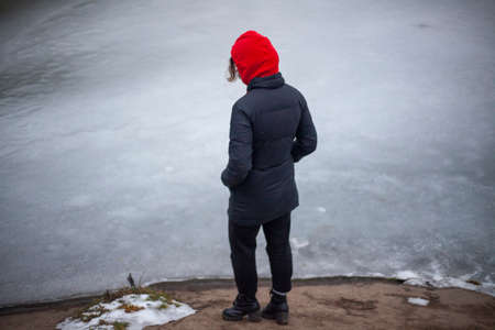 A girl in a red hood is standing by the water. Winter walk. Woman in black clothes. Loneliness in the country. Pleasant acquaintance. Beautiful face. Young lady