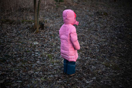 The child runs along the path. A girl walks on the street. Daughter in a long down jacket. Cheerful child on an evening walk. The mischievous tomboy. Stock Photo