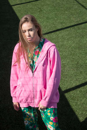 Model in a pink sweater on a green background. Beautiful model posing on the sports field. European girl shows fashionable clothes. Stylishly dressed girl with beautiful makeup.
