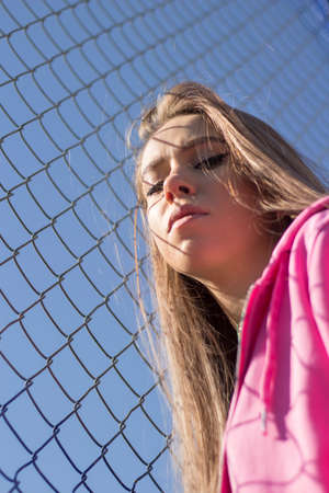 Girl near the trellised fence. Woman with long hair in a pink sweater. Sensual state of the model during shooting. Wrinkled face portrait. Beautiful makeup on the face. Mesh background when shooting.