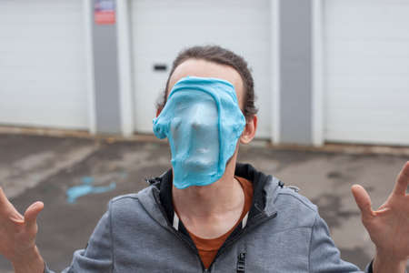A guy with mucus on his face portrays a monster. The young man is trying to scare. The man made a mask from a viscous substance and applied it to his head.