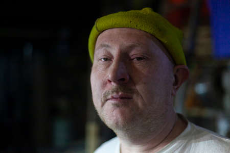 Portrait of a middle-aged man after a hard working day. The face of the master of metal. The guy in the yellow hat. Tired facial expression. Shooting indoors. Man tired of labor. A terrible hangover after alcohol. Foto de archivo