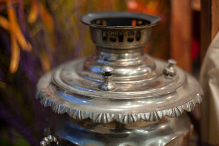 Russian samovar for tea drinking. Vintage kettle for hot water. The tradition of drinking a hot drink with sweets. Polished steel metal item.
