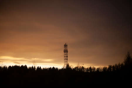 Signal transmission tower. The signal from the atomic clock. Forest at sunset. High radio tower. The object of telecommunications. High-altitude antenna transmitting magnetic waves. Sky orange Фото со стока