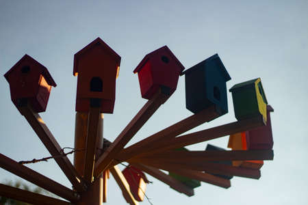 Bird houses. Colored birdhouses on the street. Decoration in the city park for feeding birds. Multi-colored small houses made of wood.