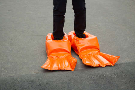 Big boots for a fun run. Doll shoes. Running with uncomfortable shoes. Funny orange rubber flippers. Stock Photo