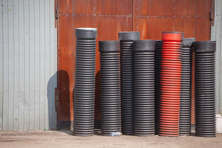 Plastic pipes for waste sewerage. Building material for laying ventilation pipes. Corrugated pipes are on the street. Banco de Imagens