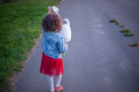 A girl in a red dress is eating cotton candy. A small child without parents in the city. Girl back to camera. The child walks on the street. Do not leave children unattended.