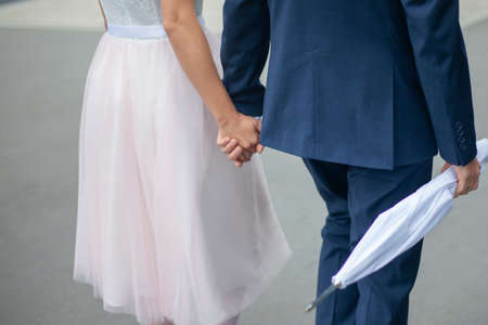 The bride and groom hold hands. A young couple is walking down the street. A man holds a white umbrella. Newlyweds walk on the asphalt.
