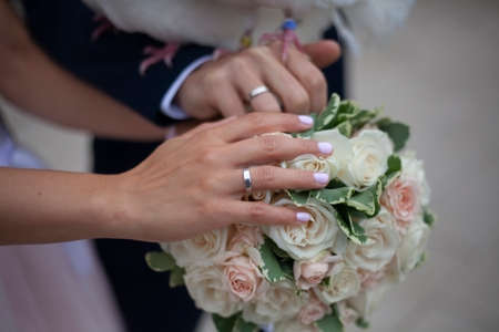 The newlyweds wore rings. Wedding rings on your fingers. The bride and groom show their hands. Wedding decoration.