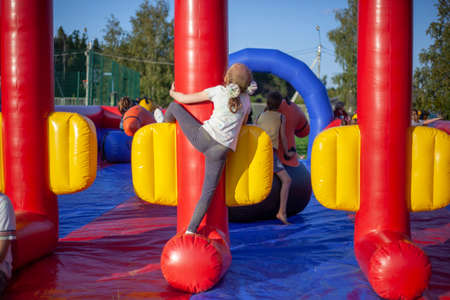 Children frolic on trampolines. Inflatable play area for children. Fun in the park. A child jumps on a soft construction installed in the park. Holiday at the child. Holidays for the whole family.