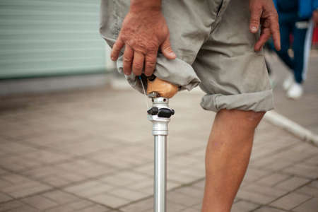 Metal prosthetic leg. Simple prosthetics for a man's leg. War invalid with a lost limb. An elderly man with a sore leg. Stand firmly on the ground. Keeping walking.