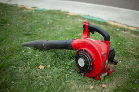 The garden vacuum cleaner lies on the grass. Blower for cleaning dry leaves. Stock fotó