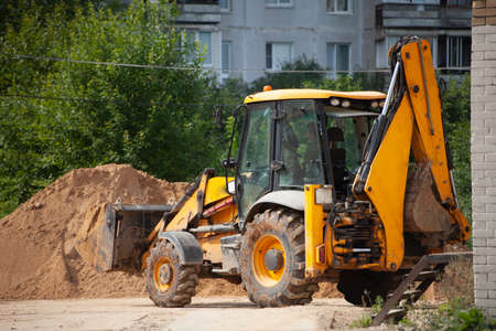 An excavator at a construction site loads sand. Construction site. Heavy machinery works outside. A mountain of sand is removed with a bucket. A worker controls construction equipment. Stock Photo