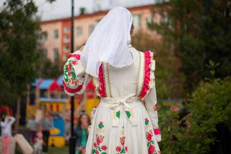 Girls in folk Russian dresses. Introduction of the folklore group on the stage. The girls are dancing. Dancers performing on the street.