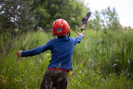 Child in a construction helmet. Orange helmet on the boy's head. The child walks alone in the summer. The boy is free.