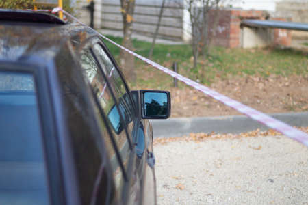 The car is parked at the red tape. Rearview mirror by the car. An old car is parked in the street.