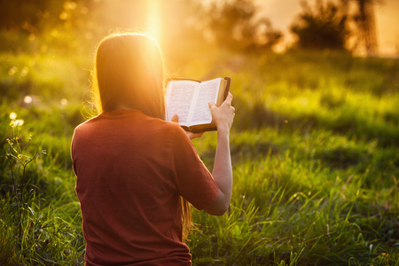 Girl reading the Bible at sunset Banque d'images