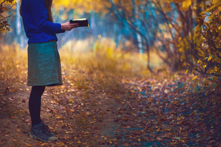 Reading the Bible in an autumn forest