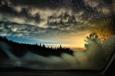 A sunset in a mountain area, seen trough the windscreen of a car, on which raindrops and steaming are visible. 写真素材
