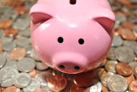 financials: Pink Piggy Bank on American Coins  Stock Photo