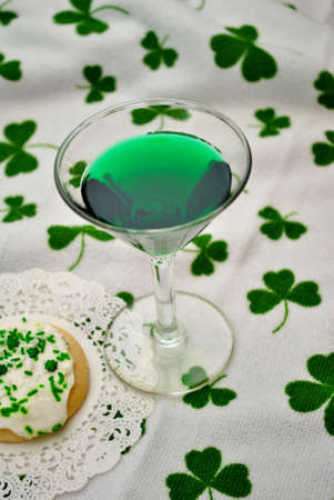 st  patty's: Green Martini Over a Shamrock Background Stock Photo