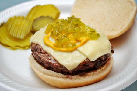carnes y verduras: Cheeseburger con el condimento, encurtidos y mostaza