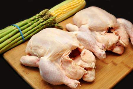 Two Raw Chickens on a Cutting Board with Asparagus and Corn Stock Photo