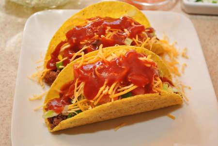 carnes y verduras: Dos tacos en un plato blanco con queso y salsa de Foto de archivo