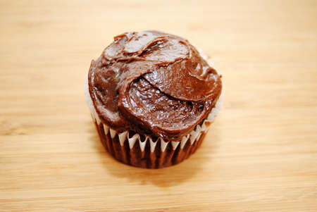 A Chocolate Cupcake with Chocolate Frosting on Wood photo