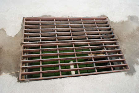 dirtied: Close-Up of a Drainage Grate to Collect Excess Water Stock Photo