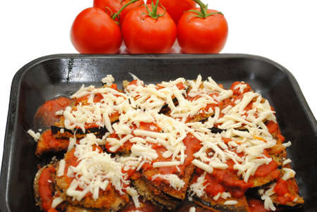 Pan of Eggplant Parmesan with Tomatoes in the Background