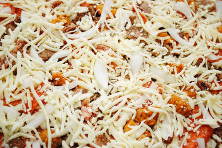 meaty: Uncooked Cheesy, Meaty Pizza Pie Covered with Cheese Stock Photo